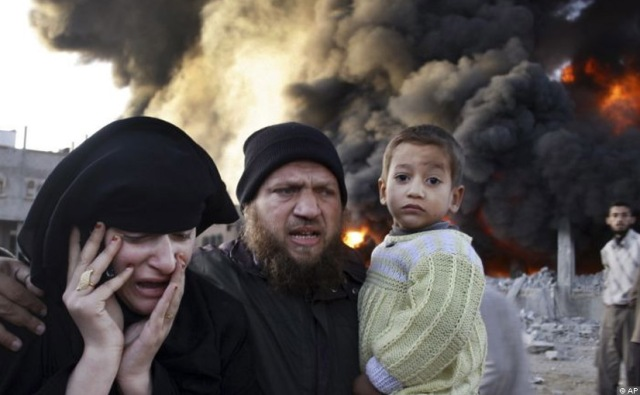 A Palestinian family rush past a burning building in the Rafah refugee camp in southern Gaza Strip after it was hit by an Israeli missile strike.