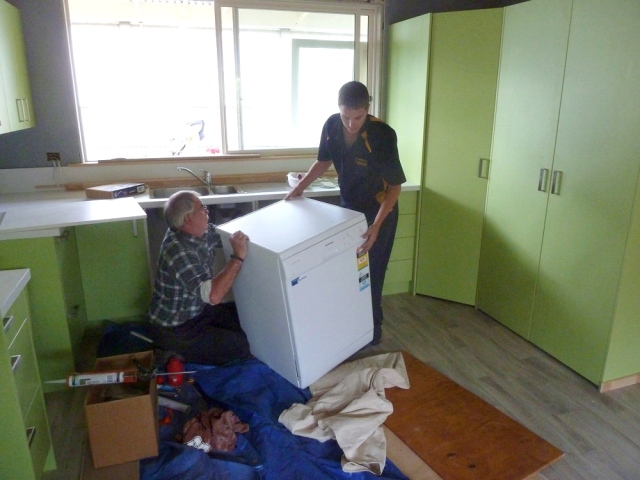 Wayne and Adrian Roper installing the new dishwasher.