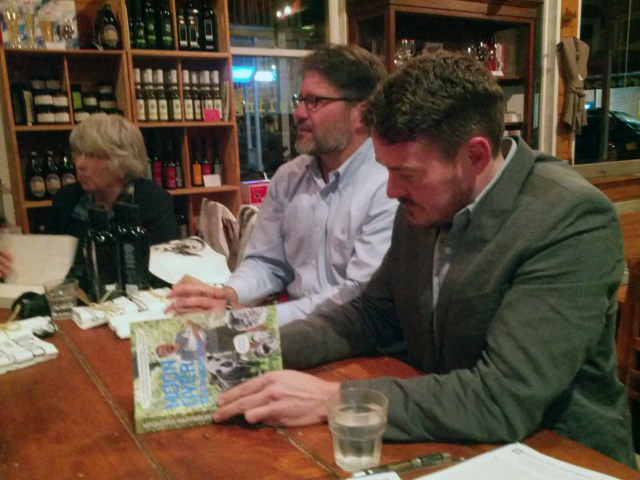 Jared Gulian signing copies of his Moon Over Martinborough book at the launch function earlier this month at the Wine Centre. His partner CJ is on his right.