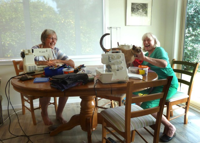 Sandy Barker, Liz MacGibbon and the omnipresent Chino doing their sweatshop thing on the dining room table. Click to enlarge.