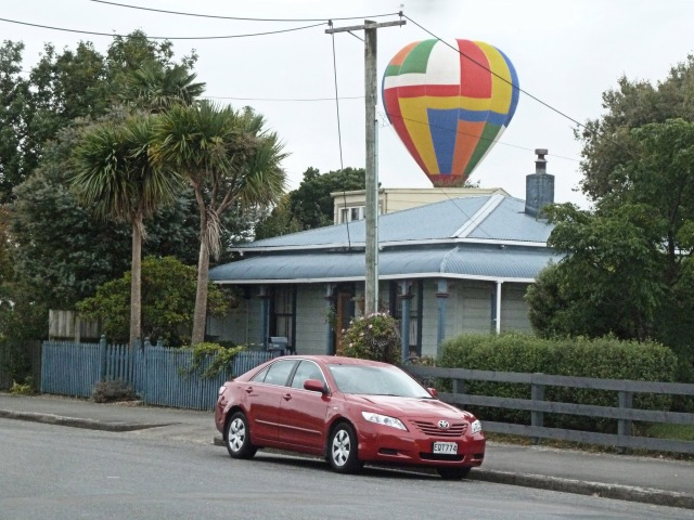 A colourful balloon passing behind a neighbour's house.