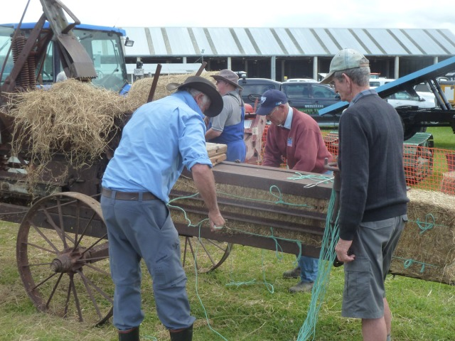 More old boys and antique toys: old-fashioned belt driven hay baler.