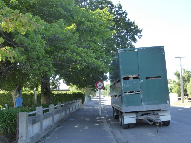 The trailer unit parked next door, shaded by the church trees.
